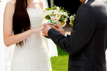 Man puts a ring on lady's hand during a wedding ceremony