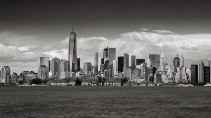 Fotomurales - Black & White time lapse of New York City's Financial District skyscrapers and clouds with Ellis Island from New York harbor