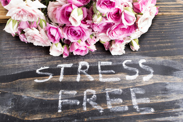 Words Stress Free with Pink Roses on a Rustic Wooden Background