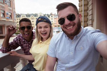 Closeup picture of young people smiling for camera. Happy friends in sunglasses making selfies onmobile or smart phone outdoors.