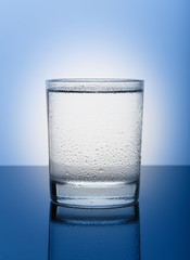 Cool glass of pure water on a blue background