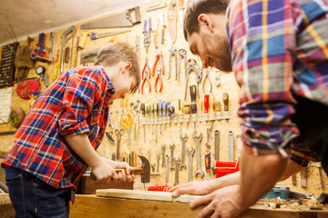 father and son with hammer working at workshop