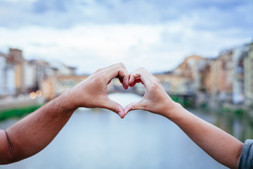 Loving couple making heart with their hands in front of Ponte Vecchio, Florence