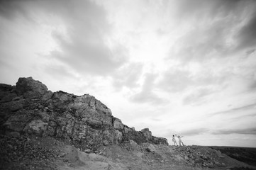 Pregnant woman and man photo shoot in a stone quarry