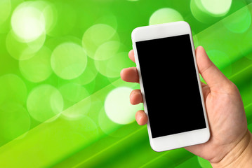Woman hand holding smartphone against green bokeh abstract backg