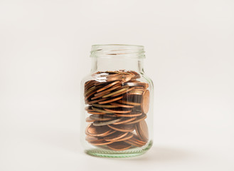 Coins in glass bottle on white background