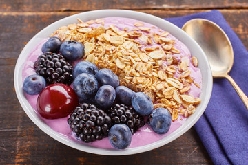 Dish of yogurt smoothie, fresh berries and muesli