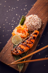 Teriyaki salmon with quinoa on a wooden platte