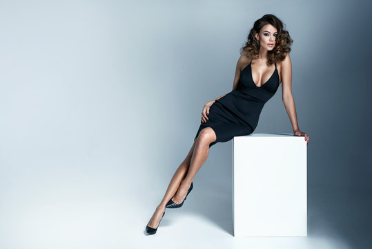 Photo of a sexy brunette woman wearing black dress