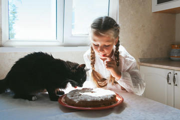 Child girl feeding a black cat in the kitchen.