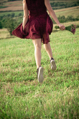 girl in red dress and sneakers run on summer field