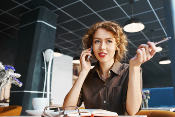 joyful smiling woman sitting in a cafe and talking by phone at a table made of wood . Business or lifestyle concept