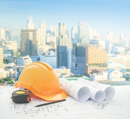architectural blueprint with safety helmet and tools over modern business district with high building