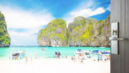 opened wooden door to beautiful beach with tourist at maya bay, phi phi leh island, thailand