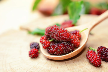 fresh red mulberries with green and yellow mulberry leaf on wooden background.
