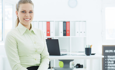 Beautiful smiling businesswoman sitting on the background of her office. Business, analytics research, excellent education, certified public accountant concept