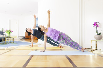 two women doing yoga at home