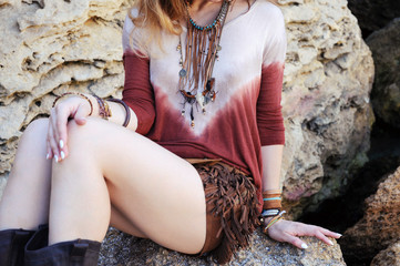 Female neck, chest and hands with boho chic bracelets and leath