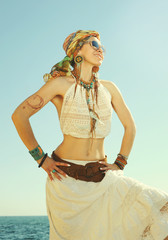 Dressed in boho chic style woman portrait, sunny  outdoor photo against sea