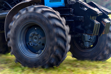 Wall Mural - Powerful tractor wheels go over the ground up dust.A small movement effect