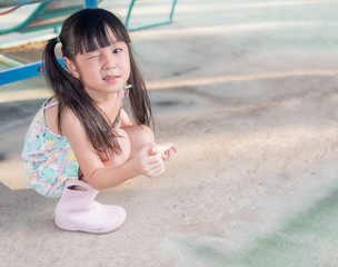 asian baby child playing on playground, close one eye