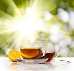 image of cups with tea and lemon on sunlight background