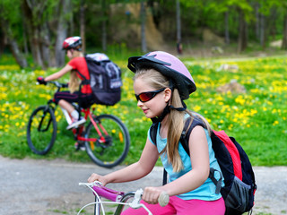 Children wearing bicycle helmet and glasses with rucksack rides bicycle. Bicyclist children is looking forwaqrd. Children ride on green grass and flowers in park outdoor.