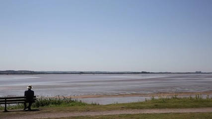 Fototapete - Lydney harbour view across the River Severn estuary towards the Severn bridge England uk with pan to picnic area and stones