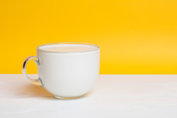Glass cup full of milk on white wooden table