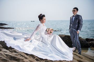 Asian couple wearing wedding dress and suit for beach wedding ceremony
