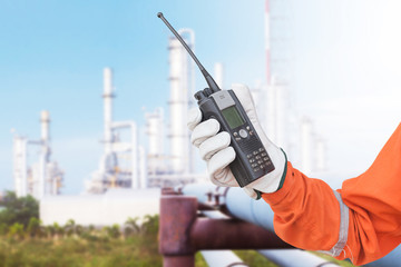 Hand hold walkie talkie oil refinery distillation towers background