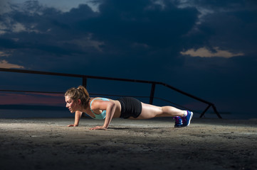 Strong fit woman doing push ups on sea pier