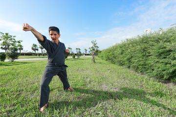 Boy in black kimono during training karate kata exercises in park