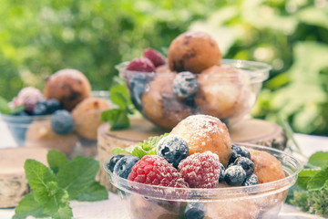 Breakfast, with cottage cheese balls with raspberry, blackberry and blueberry and mint on summer background. Toned and processing photos with soft selective focus. Shallow depth of field