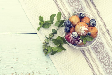 Breakfast, with cottage cheese balls with raspberry, blackberry and blueberry and mint on light table.  Toned and processing photos with soft selective focus. Shallow depth of field