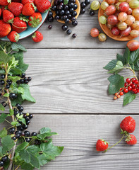 Frame from gooseberry, strawberry and branches with currants on wooden background. Close up, top view, high resolution product.