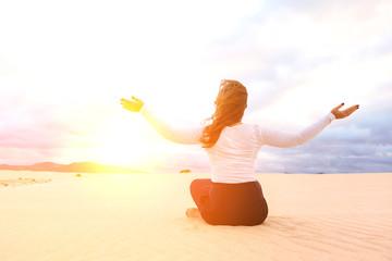 Frau meditiert in der wüste