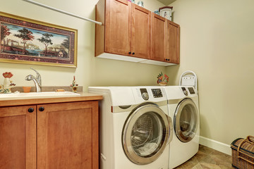Laundry room with modern appliances, brown vanity cabinet