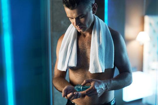 Men Skin Care After Shaving Face. Man Using Lotion In Bathroom