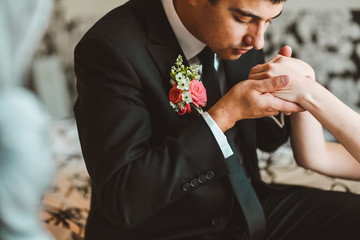 Bride and groom embracing in hotel room bed. Groom kissing bride hand.