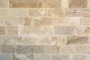 gray wall of sandstone blocks of rectangular shape with smooth edges