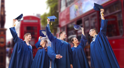 group of happy students waving mortarboards