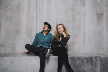 Young couple sitting in front of concrete wall