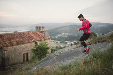 Trail runner, man on a big rock