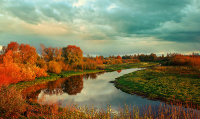 Autumn sunset landscape with river and yellowed tress