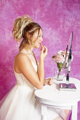Teen girl in white tulle dress sits at vanity putting on makeup in preparation for party.  Isolated on pink textured background.