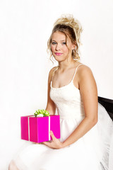 Teen girl wearing white party dress while holding onto pink gift.  Isolated on white background.  Dreamy affect