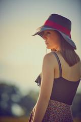 Giovane ragazza con cappello, serena al sole in campagna