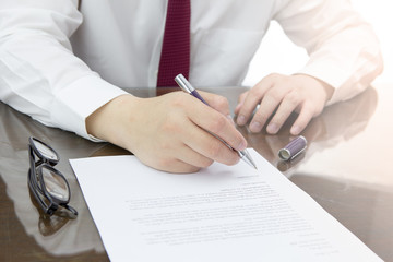 Businessman is signing a contract or resignation letter concept.