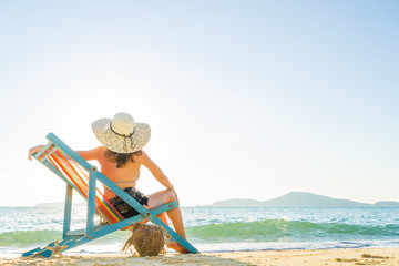 Young woman in hat sitting on beach